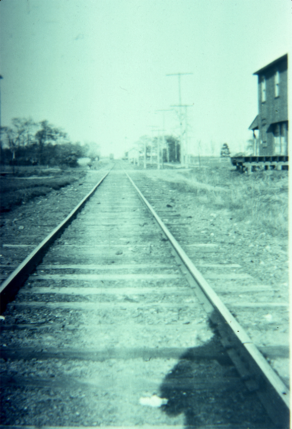View of tracks looking east at North Maple Avenue. A corner of the old soap Factory appears in the upper right corner.
